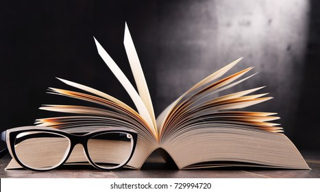 Composition with open book and glasses on the table.