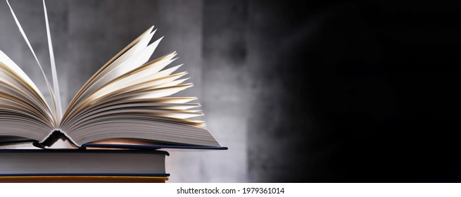 A composition with an open book lying on a stack of other books