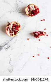 The composition of an open pomegranate and pomegranate seeds on a white marble background. Some grains are crushed, red juice on the background. Top view.