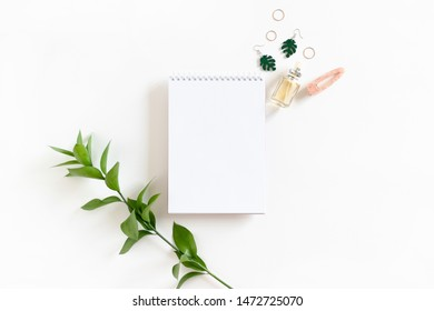 Composition with open spiral notepad, ruscus branch and women's accessories on white background