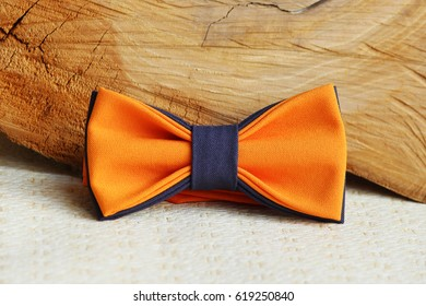 Composition: orange with a grey bow tie and wooden stick on a beige background.