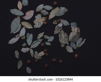 Composition of Organic Macadamia nut and bay leaf on black background, view from above.