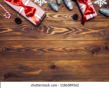 Composition of packed present boxes with pine cones, snowflakes and lollypop on wooden board. Celebrations concept