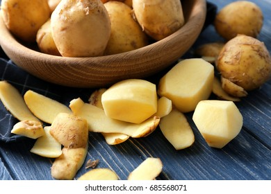 Composition with peeled potatoes on wooden table