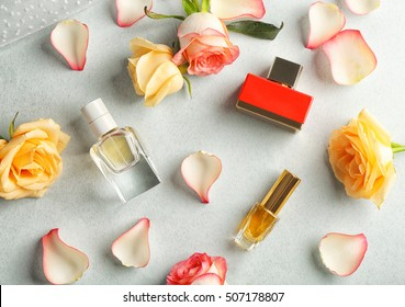 Composition of perfume bottles and roses on light background