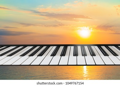 Composition of piano keyboard on marine background with a setting sun. Concept of music, nature, creation, unity of music and nature.