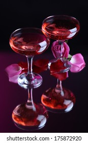 Composition with pink  wine in glasses and  rose petals on dark color background