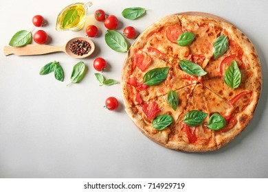 Composition with pizza, oil, cherry tomatoes and fresh basil on light background
