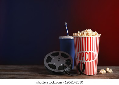 Composition with popcorn and cinema reel on table against color background. Space for text