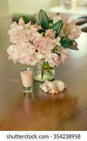 Composition of posh shot of pink liqueur with pink flowers in a background on the wooden table - focused on liqueur
