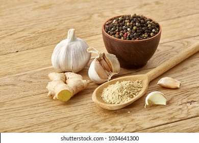 Composition of powder spices on spoon and different sorts of spicies on wooden table background, selective focus