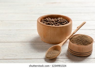 Composition with powdered pepper and corns in wooden dishware on table