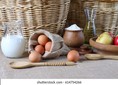 Composition of products for baking and eating. Milk, flour, oil, eggs, apples are on the table in the background of wicker baskets.