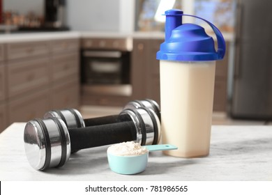 Composition with protein powder, shake and dumbbells on table