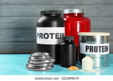 Composition with protein powder, weight plates and pills on wooden background