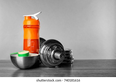 Composition with protein shake, powder and dumbbell on table