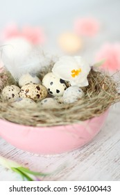 composition with quail eggs, white crocus flowers, pink bowl and hay nest on light wooden background. rustic, shabby chic, country easter, spring decor, card