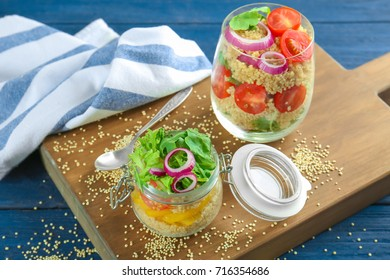 Composition with quinoa and vegetables in glassware on table