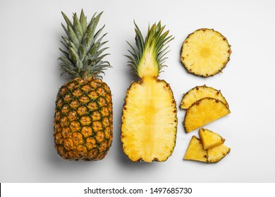 Composition with raw cut pineapples on white background, top view