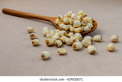 Composition of raw lotus seeds .The asian popular seed for food ,desserts and herbal medicine in wooden spoon on brown background.