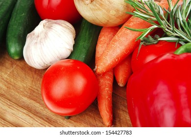 Composition with raw vegetables on kitchen cut board isolated over white background