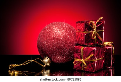 Composition of red christmas ball and small gift boxes on gradient background