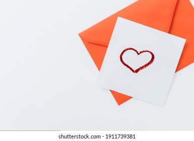 The composition is a red heart and an envelope on a white background.flat lay.copy space. Love, friendship, and a declaration of love.Happy Valentine's Day.Women's Day.Minimal, stylish holiday concept