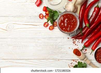 Composition with red hot sauce and ingredients on wooden background