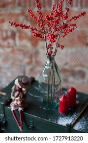 Composition with a red ilex branch, two candles and an interior doll. A branch of ilex stands in a bottle. The composition includes a wooden box. Image with selective focus.