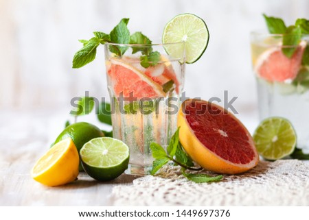 Composition with refreshing healthy alcohol free home made citrus lemonade with pepper mint, limes, lemons, pomelo. White lace napkin as decor, wooden background. Vacation mood, enjoying summertime