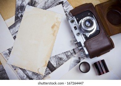 Composition of retro camera with film strip and old photographs