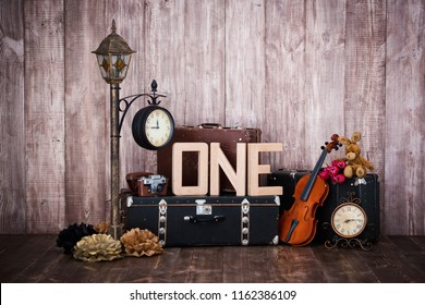 Composition in retro style, old suitcases, a lantern with a clock, a violin and a word one
