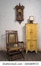 Composition of retro wooden rocking chair, yellow cupboard and pendulum clock in living room