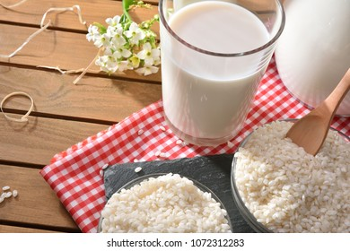 Composition with rice drink in containers on wood table in the field. Alternative milk. Elevated view. Horizontal composition