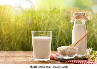 Composition with rice drink on wooden table in the field. Alternative milk. Front view. Horizontal composition