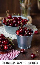 Composition with ripe cherries in metal bowls and clay brown plate. Vintage napkins as decor. Dacha style, countryside, cozy and cute, grandmother's kitchen. Dry flowers in vase on background
