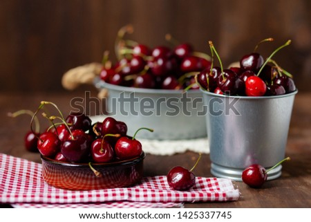 Composition with ripe cherries in metal bowls and clay brown plate. Vintage napkins as decor. Dacha style, countryside, cozy and cute, grandmother's kitchen