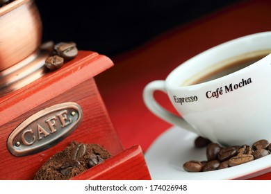 composition of Roasted coffee beans in front ot Coffee Grinder and white coffee cup