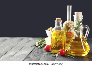 Composition with rosemary oil and tomatoes on wooden table