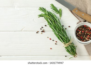 Composition with rosemary, pepper, knife and towel on white background