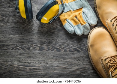 Composition of safety workwear on wooden board.