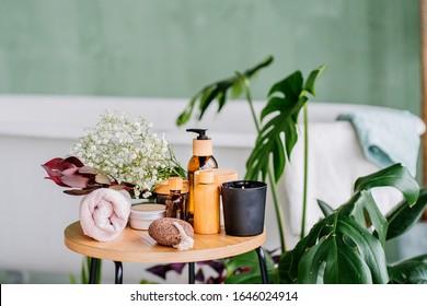 Komfortable Wellness-Set auf Holztisch in modernem öko-natürlichen Innenraum des Badezimmers mit grünen Pflanzen. Umweltfreundliche natürliche Reinigungsmittel und -produkte.