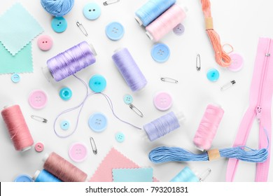 Composition with sewing threads and accessories on white background, top view
