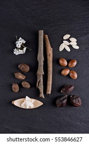 Composition of shea butter and nuts, argan fruits and seed on a black background. Flat lay