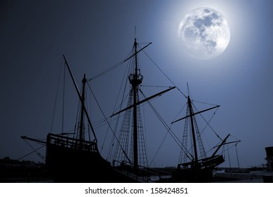 Composition with a silhouette of an old discovery times caravel in a full moon night.