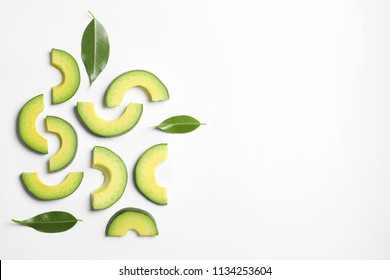 Composition with sliced ripe avocado on white background