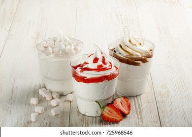 composition with soft ice cream. on a wooden background. strawberry, caramel and with marshmallow