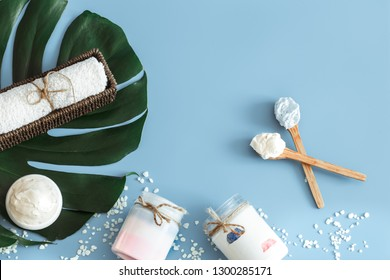 Composition of spa items on a color blue background with a tropical leaf, the concept of body care and spa treatments