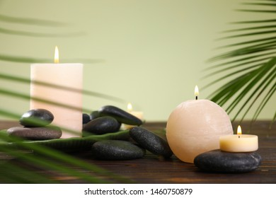Composition of spa stones and burning candles on wooden table against light green background