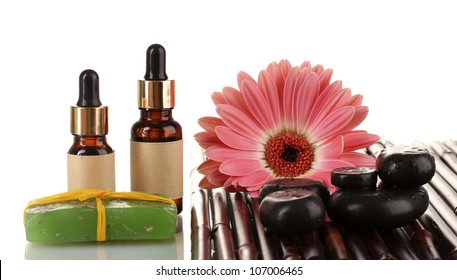 Composition of spa stones, essential oil and gerbera on bamboo mat on white background